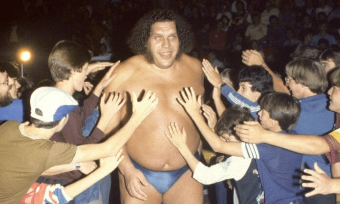 Andre the Giant waling through a crowd of fans on the way to the ring. Fans are all reaching out to touch him.