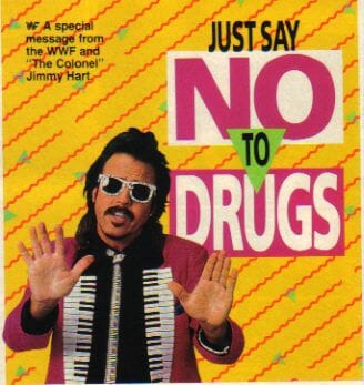 Jimmy Hart in a Jacket with piano keyboard lapels and sunglasses holding his hands up in a Just say NO to Drugs ad