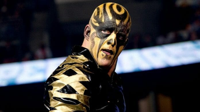 Dustin Rhodes as Goldust in black and gold face paint and leather jacket