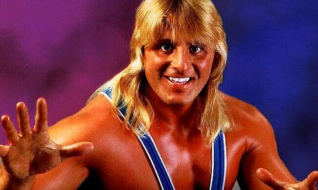 Owen Hart in wrestling outfit with hands up in article where Owen Hart talks about his career