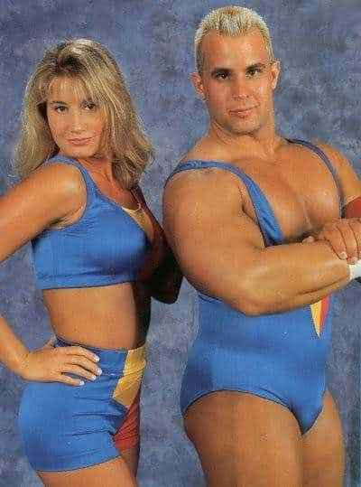 Tammy Sytch and Chris Candido in matching blue, yellow and red wrestling attire standing sideways posting for the camera