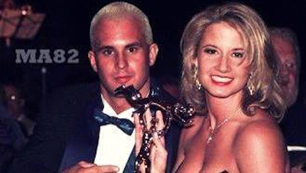 Chris Candido (Skip) in a tuxedo and Tammy Sytch (Sunny) dressed in a black strapless dress holding an award
