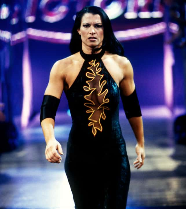 Lisa Marie Varon walking on stage in a black wrestling unitard with a sheer burnout along the chest