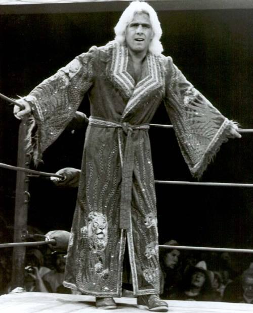 Rick Flair in his younger days standing in the ring in a sequined robe with lion heads on the bottom