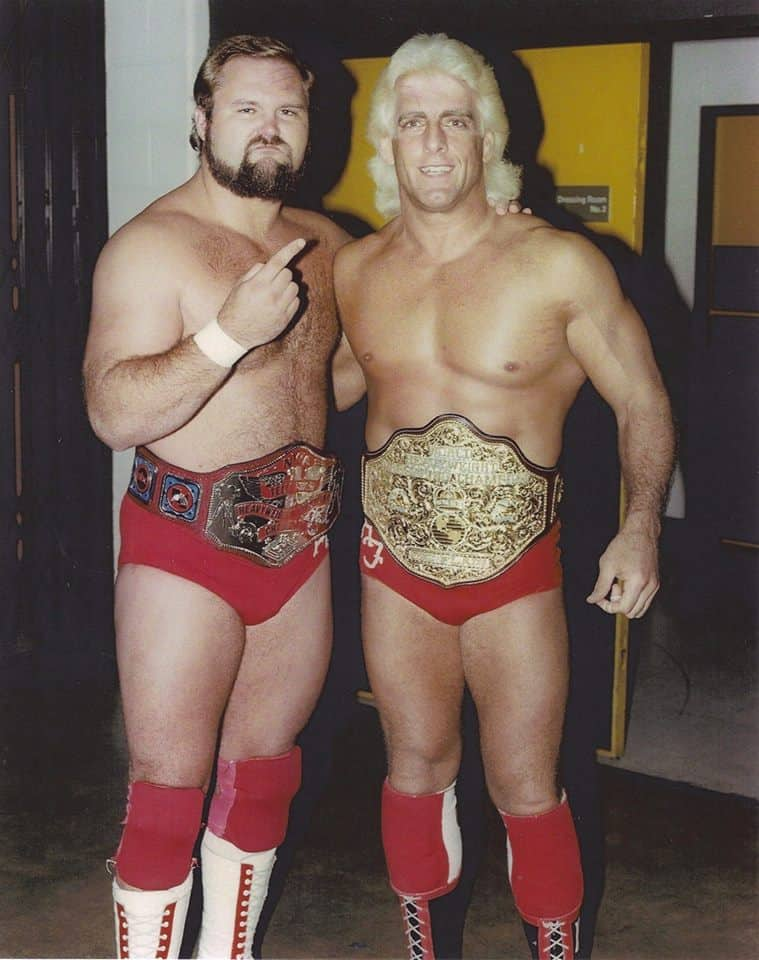 Arn Anderson pointing at Flair with #1 sign both wearing title belts