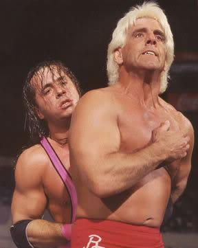 Ric Flair vs Bret Hart during a match with Hart holding Flairs arm behind his back