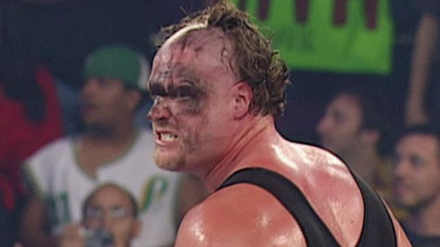 Kane in the ring sweating with black eyeliner running all down his face