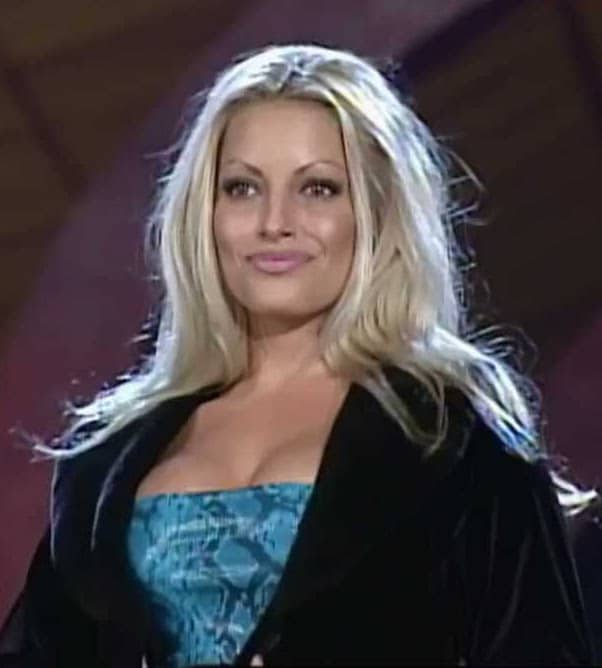 Trish Stratus in a black Jacket and blue snake skin tube top