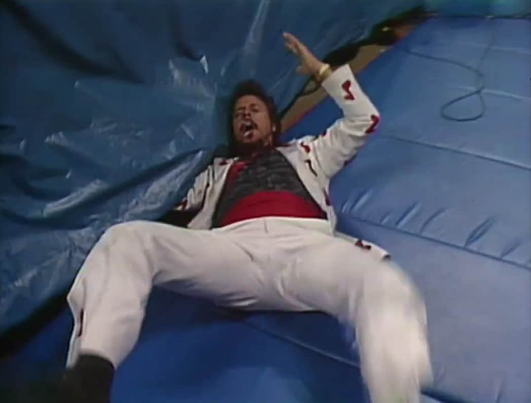 Jimmy Hart on the floor after being attacked by The British Bulldogs Mascot Matilda