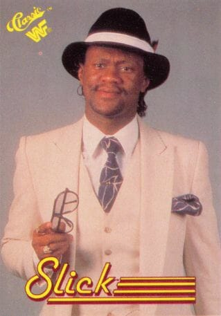 Wrestler Slick in a promo shot wearing a tan suit with a black and white fedora
