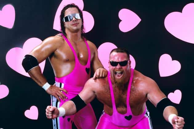 The Hart Foundation posing in front of pink hearts in their signature hot pink costumes