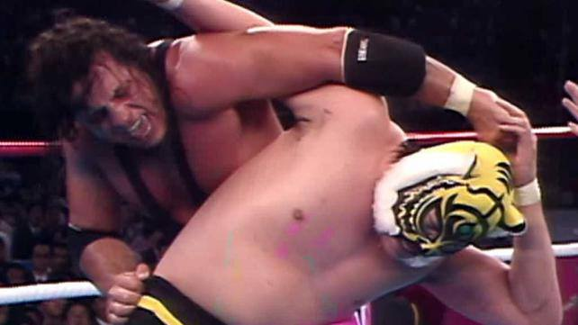 Bret Hart wrestling with a yellow tiger masked opponent in Japan