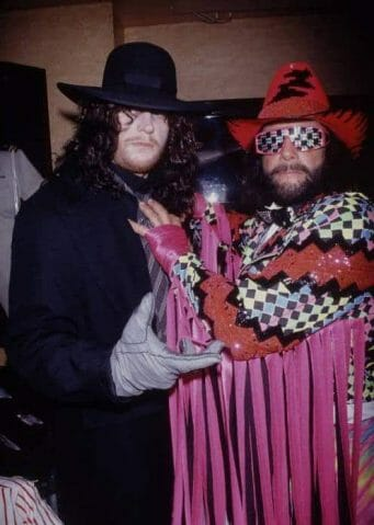 The Undertaker posing with Macho Man Randy Savage who dressed in a red and black cowboy hat and a flashy sequin jacket with pink fringe.