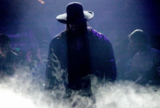 The Undertaker in low light walking through fog in an arena