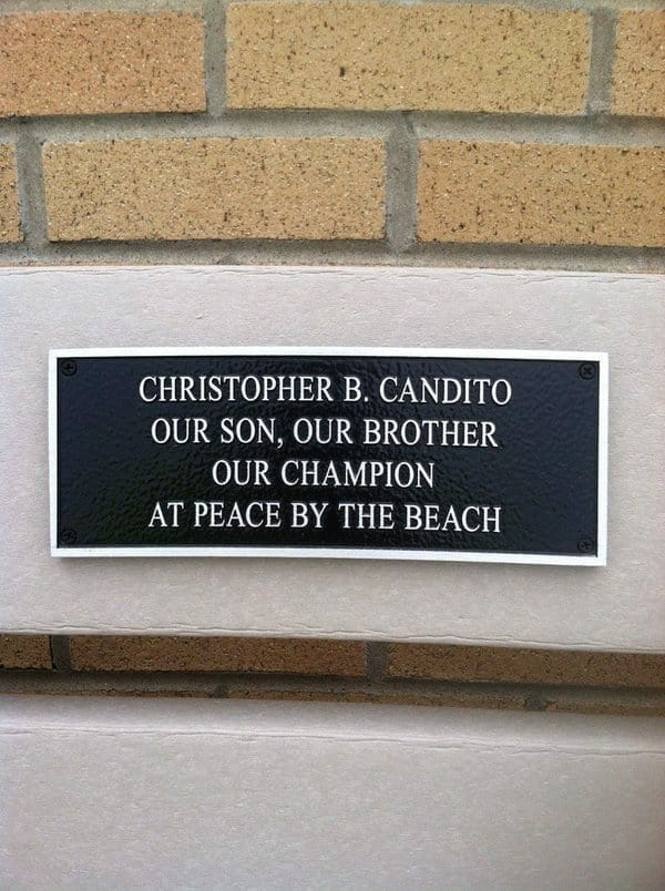 A plaque on a bench dedicated to the memory of Chris Candido on Spring Lake beach, New Jersey.