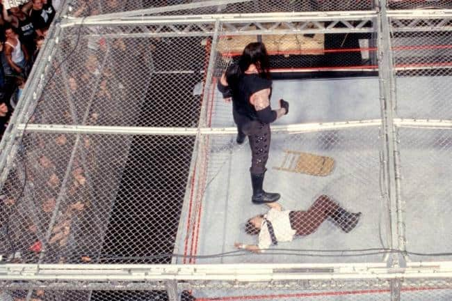 The Undertaker gazes down at the limp body of Mick Foley after taking his now-legendary fall through the Hell in a Cell cage.