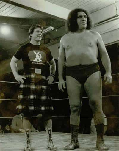 Andre the Giant and Rowdy Roddy Piper standing inside a ring and smiling