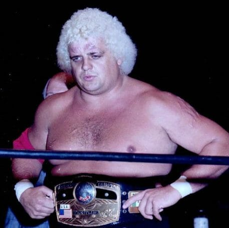 Dusty Rhodes in the ring with a title belt on
