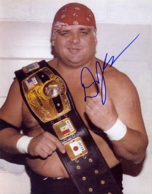 Dusty Rhodes autographed photo of him with a title belt wearing a red bandana and wrestling trunks