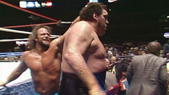 Randy Savage in a fight with Andre The Giant pulling his hair outside the ring