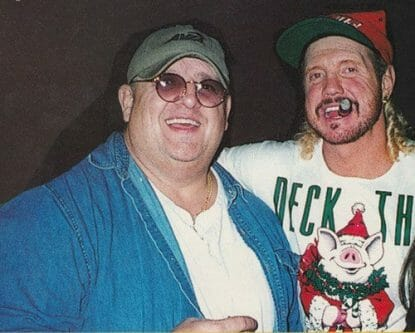 Dusty Rhodes in a Christmas hat and shirt smoking a cigar with his arm around Diamond Dallas Page