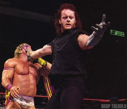 The Undertaker playing to the crowd as he holds the face of the Ultimate Warrior in 1991