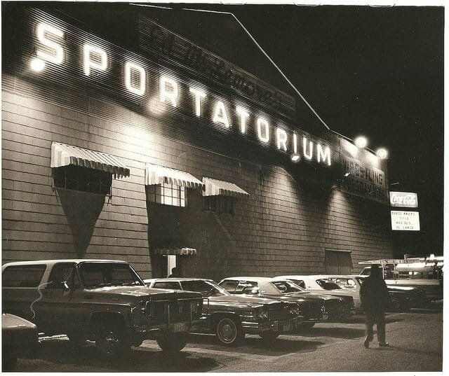 Black and White photo of the Dallas Sportatorium at night with cars from the 1970s lined up in front.