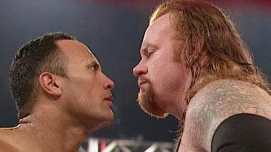 The Rock and The Undertaker staring each other down.