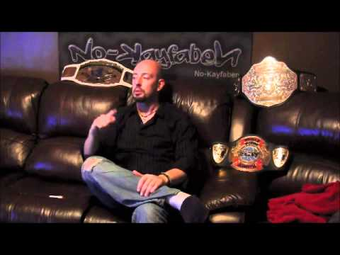 Justin Credible sitting on a black leather sofa in jeans and a black shirt surrounded by his belts.