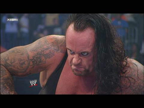 An Angry Undertaker in a black sling that shows his tattooed arms.
