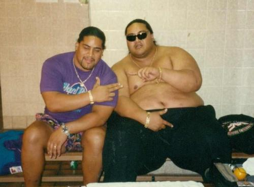 Yokozuna with his cousin Rikishi backstage sitting on a bench