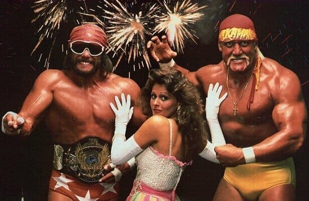 Miss Elizabeth with her hands on the chests of her husband Randy Savage and Hulk Hogan who look angry and tense as if she's stopping them