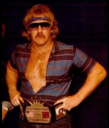 Randy Rose, founding member of The Midnight Express, in sunglasses, a shirt unbuttoned and his title belt on