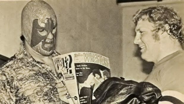 Don Jardine (left) before he was The Spoiler workingunder a hood as The Super Destroyer looks at a wrestling magazine with Lord Alfred Hayes. Photo credit: Mike Mooneyham