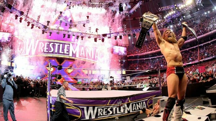 Daniel Bryan, one of the greatest WWE Champions, holding up his title belts outside the ring with smoke pyrotechnics in the background going off after WrestleMania 30, WrestleMania xxx