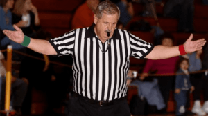 Wrestling Referee with whistle in his mouth and hands up