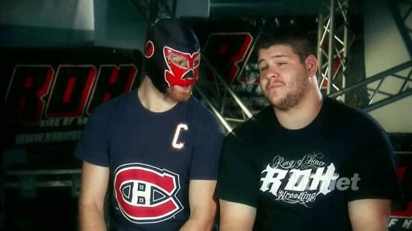 Kevin Owens and Sami Zayn in his El Generico Mask sitting down for an interview