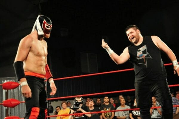 Kevin Owens (then Kevin Steen) in the ring shooting a bird to Sami Zayn (then in a mask as El Generico)