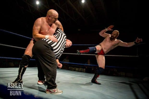 Brutal Bob Evans holds Bobby Mathews in an abdominal stretch while Tough Tim Hughes gives him a thrust kick to the face following the main event at Southern Legacy Wrestling's Nov. 4, 2017 show.