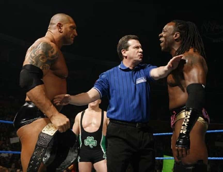 Dave Bautista holding a title belt and Booker T yelling at him while a ref stands in between with arms across both mens chests