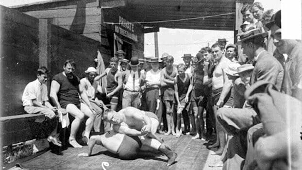 Photo of wrestlers having a match at a carnival with lots of onlookers to answer the question when did wrestling begin