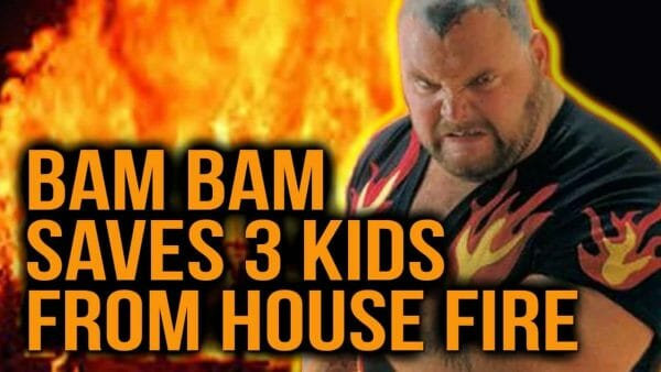 Photo of Bam bam Bigelow wearing a black t-shirt with flames on it with fire in the background.