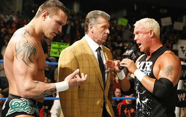 Randy Orton looking at his hand dazed while Mr. Kennedy talks on the WWE Mike with the MC