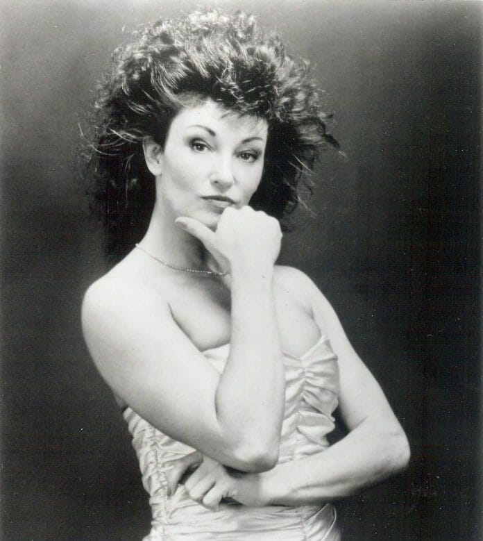 Black and White headshot of Sherri Martel in a satin strapless gown and her hand on her chin as if contemplating