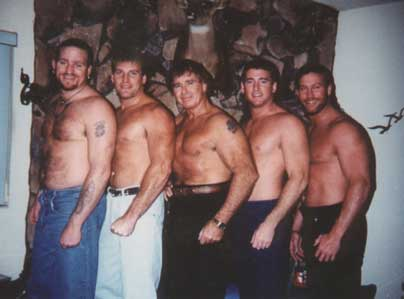 "The original Bullet club: ""Road Dogg"" Brian James, Steve, Bullet Bob, Scott, and Brad part of the Armstrong wrestling family posing with no shirts and pants in their home"