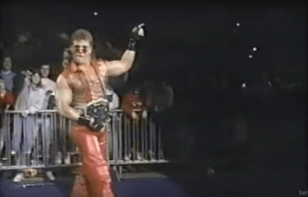 Shawn Michaels struting in a copper colored vest and pants wearing his title belt in 1993
