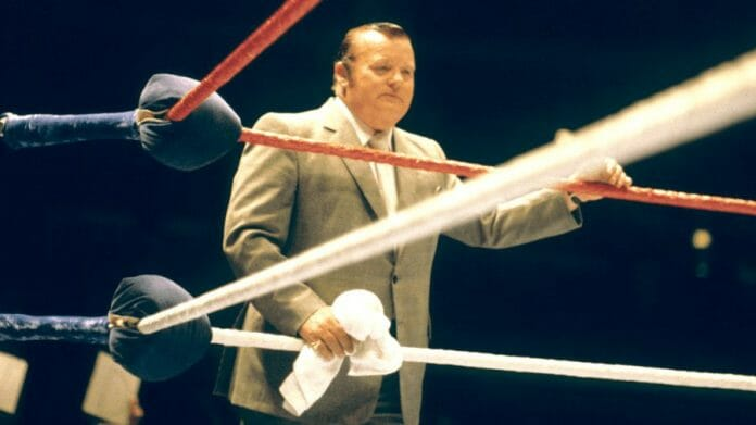 Arnold Skaaland, manager for WWF Champion Bob Backlund, on our best heel wrestler list, standing by the ring in a tan sports coat holding a towel