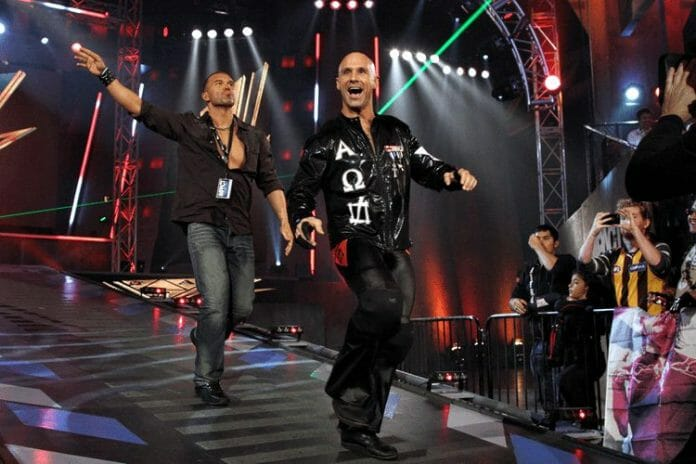 "Frankie Kazarian and Christopher Daniels as part of Bad Influence enter on a stage to wrestling music ""Devious"" to laser lights"