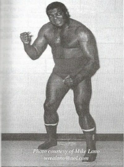Black and White Photo of BoBo Brazil posing in his wrestling trunks with fist in the air smiling
