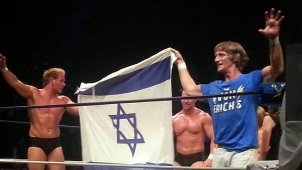 Kevin Von Erich with his sons, Ross and Marshall holding up an Israeli flag in the ring in Tel Aviv, Israel, July 9th, 2017